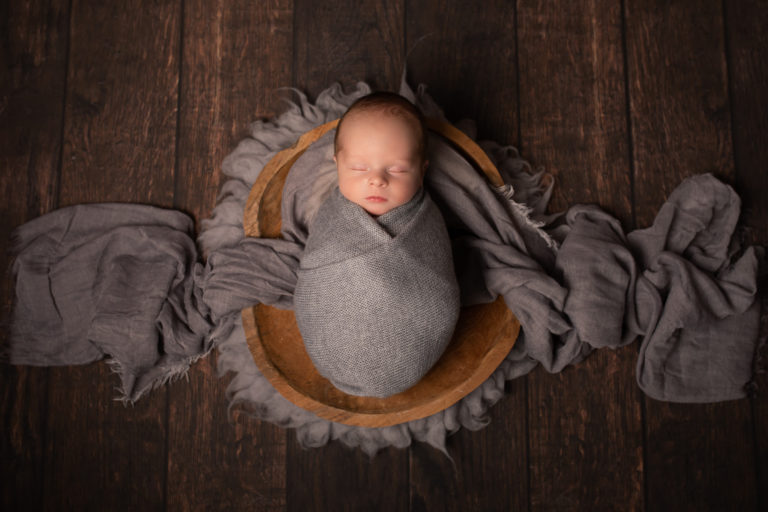 Newborn baby boy photographed in Strood. Boy is wrapped in grey wrap on a beautiful wooden floor