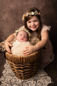 Sibling photo. Newborn wrapped in a cream blanket with older sister snuggling in. Photographed in Medway Kent