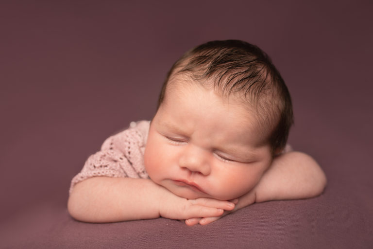 Newborn baby girl photo on pink background. Head on hands