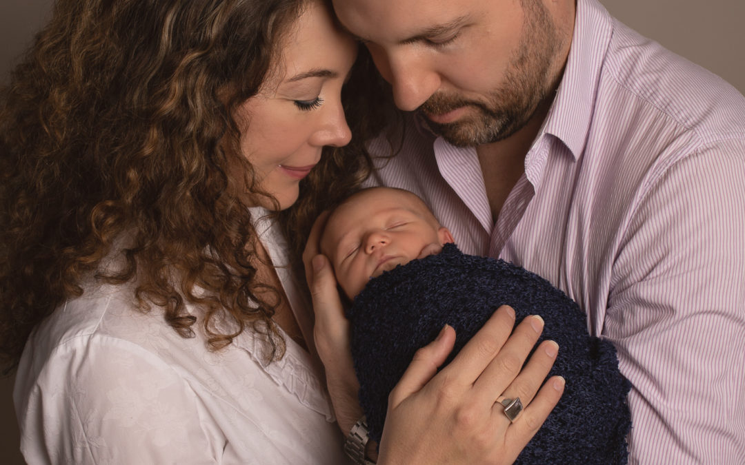 Parent photo with newborn baby boy in dads arms with mum cuddling in. Newborn photo medway