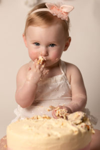 Cake Smash for babies first birthday. Baby girl wearing white romper and pink headband eating and smashing cake.