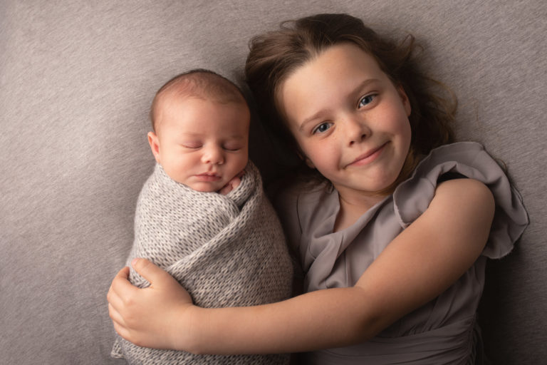 Sibling photo. Big sister holding newborn baby who is wrapped. Photographed by Hannah Cornford Photography in Strood