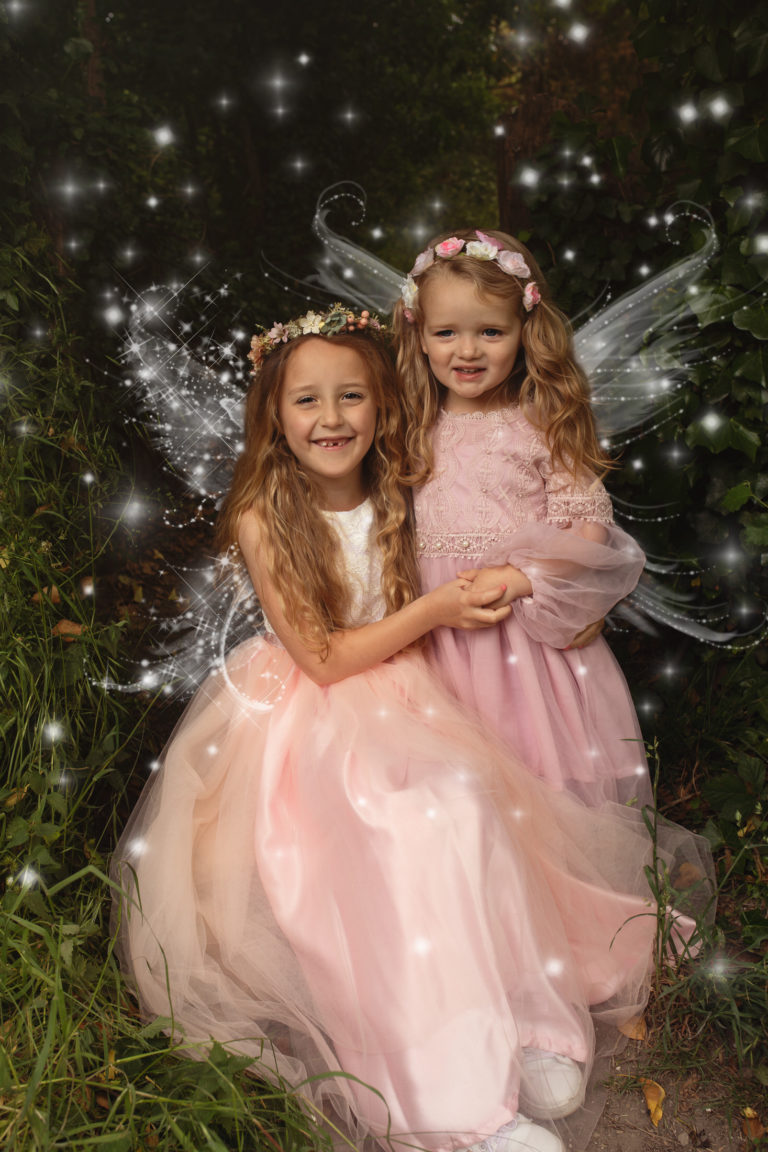 Fairy photoshoot - two girls wearing pretty pink dresses with fairy winds and added sparkle. Photographed in Medway, Kent.
