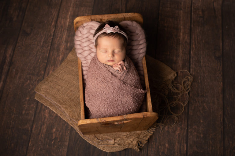 Newborn baby girl photo. Wrapped up in a pink wrap in wooden bed.