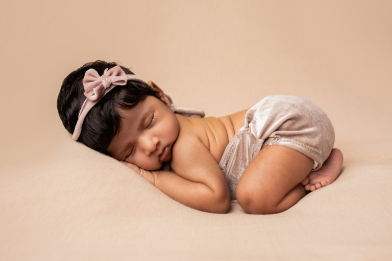 Newborn baby girl photo . Curled up on her belly wearing a pink headband and outfit