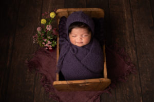 Newborn photo baby girl Strood, Medway. Wrapped in purple in a wooden bed