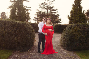 Maternity Photoshoot - Pregnant Lady wearing red dress and dad in a suit. Holding baby bump in Danson park