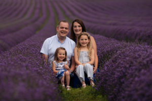Family photoshoot Kent Lavender fields. Parents with their two girls sitting together in a field full of lavender