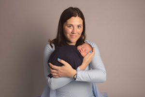 New mum holding her newborn son - Mum is wearing light blue dress with newborn wrapped in a navy wrap.. Photographed in Medway, Kent