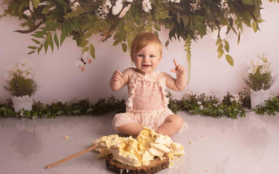 Cake Smash photo of One year old girl in pink outfit. There is a smashed cake and wooden spoon and she is cheering.